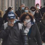 People wearing protective face mask walk and shop in the center of Milan, Italy, 25 January 2021. In Italy, the orange zones (medium-high risk) , as the Lombardy Region, stipulates that shops can open, while restaurants and bars are closed except for takeaway. ANSA/DANIEL DAL ZENNARO