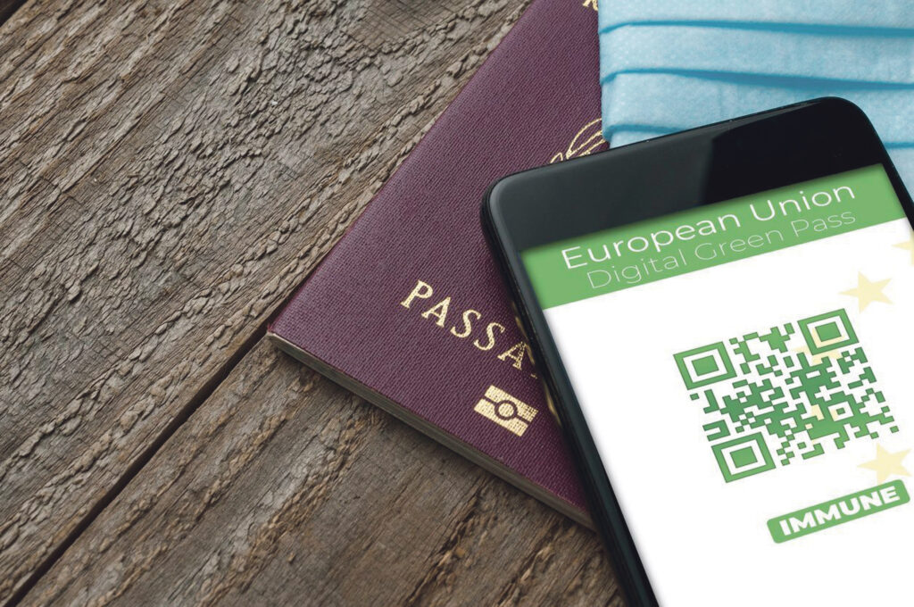 Digital Green Pass concept: Smartphone over a passport and a surgical mask on a wooden table show an hypotetical app for the Digital Green Passport (or digital pass certificate) (Digital Green Pass concept: Smartphone over a passport and a surgical ma